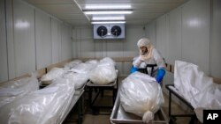 "Seorang pekerja dari ""Hevra Kadisha,"" komunitas pemakaman resmi Yahudi, sedang mempersiapkan jenazah di kamar jenazah khusus korban Covid-19 di Kota Holon, dekat Tel Aviv, Israel, Senin, 12 Oktober 2020. (Foto: AP)"
