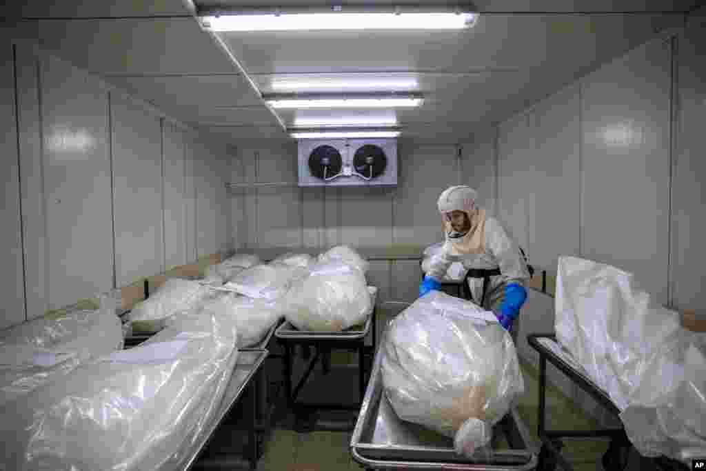 """A worker from """"Hevra Kadisha,"""" Israel's official Jewish burial society, prepares bodies before a funeral procession at a special morgue for COVID-19 victims,in the central Israeli city of Holon, near Tel Aviv."""
