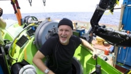 Filmmaker James Cameron emerges from the Deepsea Challenger after his successful solo dive to the Mariana Trench, the deepest part of the ocean. The director has donated the vessel to the Woods Hole Oceanographic Institution.