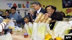 باراک اوباما و خانواده اش روز چهارشنبه در یک مرکز امداد محلی، مواد غذایی مربوط به روز شکرگزاری را در میان مستمندان تقسیم کردند