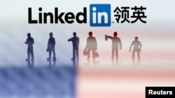 FILE - Small toy figures are seen between displayed U.S. flag and Linkedin logo in this illustration picture.
