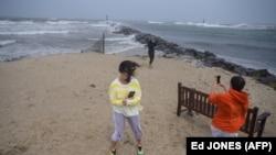 Orang-orang menyaksikan ombak saat mereka berdiri di pantai menjelang Badai Tropis Henri di Montauk, Long Island pada 22 Agustus 2021.