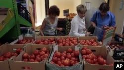 Ibu-ibu berbelanja tomat di sebuah pasar di Moskow, Rusia (7/8). Rusia melarang produk-produk pertanian dari Uni Eropa, AS, Australia, Kanada dan Norwegia.