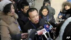 In this 2009 file photo, Zhao Lianhai, center, the father of a girl sickened after she drank tainted milk formula, speaks to journalists outside a court in China's Hebei province. Zhao, who organized a support group for parents of children sickened in one