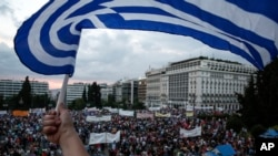 FILE - A protester waves a Greek flag during an anti-austerity rally in front of the parliament building in Athens, Greece, June 21, 2015.