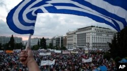 FILE - A protester waves a Greek flag during an anti-austerity rally in front of the parliament building in Athens, Greece.