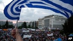 Une foule assemblée devant un drapeau grec en face du bâtiment du parlement à Athènes, Grèce, 21 Juin 2015.