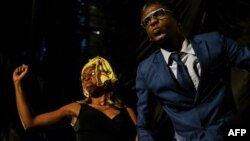 """L'actrice de théâtre Carol Magenga interprète l'ex-première dame du Zimbabwe Grace Mugabe et l'acteur de théâtre Khetani Banda dans le rôle de l'ancien président du Zimbabwe Robert Mugabe lors d'une pièce satirique intitulée """"Operation Restore Regasi"""" au"""