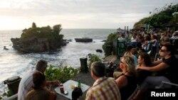 Wisatawan asing menikmati pemandangan saat matahari tenggelam di Pura Tanah Lot, Bali. (Foto: ilustrasi)