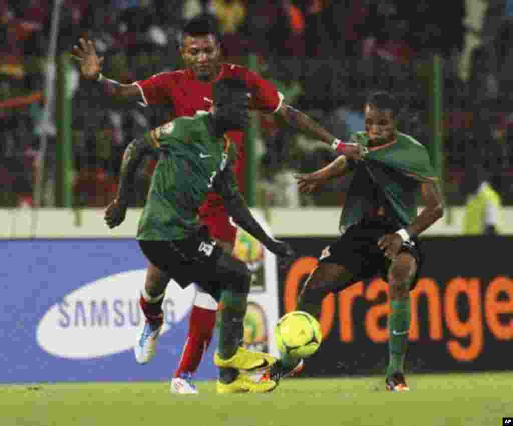 Chisamba Lungu (front) of Zambia controls the ball next to teammate Davies Nkausu (R) and Bladmir Ekoedo of Equatorial Guinea during their African Nations Cup soccer match in Malabo January 29, 2012.