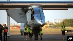 FILE - Ground crew push the Solar Impulse 2, a solar-powered airplane, toward the hangar after landing at the Kalaeloa Airport in Kapolei, Hawaii, July 3, 2015.