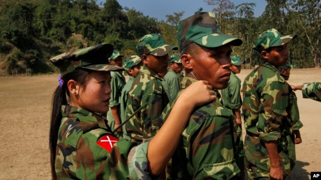 In this photo taken on Monday, Feb. 13, 2012, recruits of the Kachin Independence Army, one of the country's largest armed ethnic groups, receive training from a female instructor, left,  at a military camp near Laiza.