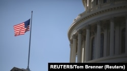 USA, Washington, The American Flag flies at the U.S. Capitol