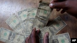 FILE: In this Friday, July 2, 2010 picture an unidentified man shows dirty one dollar notes before washing them in Harare, Zimbabwe. (AP Photo/Tsvangirayi Mukwazhi)