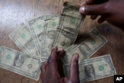 FILE: In this Friday, July 2, 2010 picture an unidentified man shows dirty one dollar notes before washing them in Harare, Zimbabwe. The washing machine cycle takes about 45 minutes.
