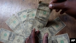 FILE: In this Friday, July 2, 2010 picture an unidentified man shows dirty one dollar notes before washing them in Harare, Zimbabwe.