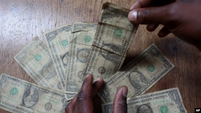 In this Friday, July 2, 2010 picture an unidentified man shows dirty one dollar notes before washing them in Harare, Zimbabwe. (AP Photo/Tsvangirayi Mukwazhi)