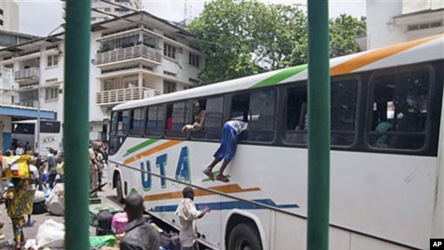 With possessions balanced on their heads, about 1,000 people frantically crowded around buses rented by Mali to evacuate its citizens from Abidjan, Ivory Coast, including a Malian man climbing into the window of a bus, March 25, 2011