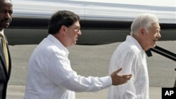 Followed by Cuba's Foreign Minister Bruno Rodriguez, former President Jimmy Carter (r) arrives to the Jose Marti airport in Havana, March 28, 2011