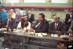 The four black men who were denied service at the Woolworth store in Greensboro, NC thirty years ago, take their places at the same lunch counter to recreate their sit-in, Feb. 2, 1990.