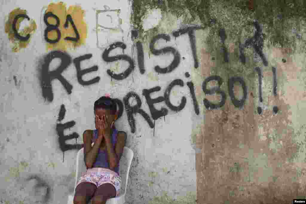"A girl sits in front of a wall with graffiti that reads, ""We must resist,"" in Metro slum near Maracana stadium in Rio de Janeiro. Residents are protesting eviction from their homes. The removal of the community is part of the renovation works of the area for the 2014 World Cup."