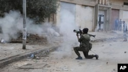 FILE - A Libyan military soldier fires his weapon during clashes with Islamic extremist militias in Benghazi, Libya, Oct. 30, 2014.
