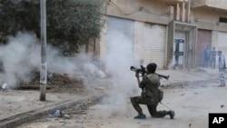 Seorang tentara Libya menembakkan senjatanya dalam bentrokan dengan milisi Islamis di Benghazi (30/10). Milisi Islamis masih menguasai sebagian besar wilayah di Libya.