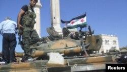 Anggota Laskar Pembebasan Suriah berdiri di atas tank yang berhasil mereka rampas dari pasukan Suriah di Aleppo (19/7).