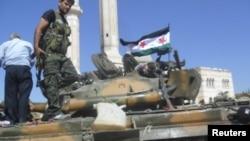 Anggota pasukan pembebasan Syria (Free Syrian Army) di atas tank di Azzaz, provinsi Aleppo (Foto: Reuters)