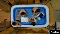 College students cool themselves inside an inflatable pool during the summer heat, at their dormitory in Wuhan, Hubei province, August 5, 2014.
