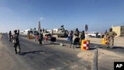 反政府武装守卫在9月12日遭到卡扎菲部队袭击的炼油厂外