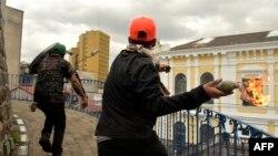 Manifestantes lanzan una bomba incendiaria casera al edificio de la Contraloría General de la nación en Quito, Ecuador, en el décimo día de protestas por un alza de precio a los combustibles decretada por el gobierno. Oct. 12 de 2019. AFP/Rodrigo Buendía.