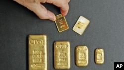 A one-ounce gold bar [top R] designed by fashion designer Jean Paul Gaultier is displayed with gold bars weighing between one ounce and 500 grams in an office of French gold supplier CPoR Devises company in Paris, October 10, 2011.