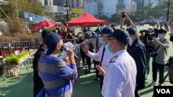 香港支聯會主席李卓人(左)就維園年宵攤檔被終止合約,一度與到場進行清場行動的食環署職員發生爭執。(美國之音 湯惠芸拍攝)