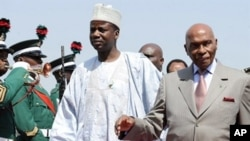 Senegalese President Abdoulaye Wade (R) and Nigerian Foreign Affairs State Minister Aliyu Idi Hong arrive in Abuja Airport to attend a special summit of Economic Community of West African States (ECOWAS), 7 Dec 2010
