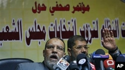 Members of the guidance council of Egyptian biggest opposition group, the Muslim Brotherhood, Essam el-Erian, left and its spokesman Mohammed Morsi attend a press conference alleging early fraud in Egypt parliamentary elections, in Cairo, Egypt, 22 Nov 20