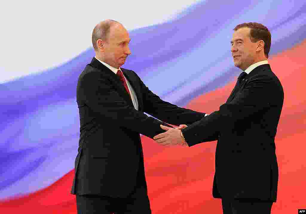 Russian President Vladimir Putin, left, and former President Dmitry Medvedev shakes hands at the inauguration ceremony. (AP)