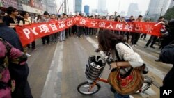 """A protest against a PX chemical plant in the city of Ningbo in Zhejiang province. The banner reads: """"Project PX get out of Ningbo, Ningbo people stand up."""""""