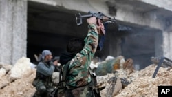 FILE - Syrian soldiers fire their weapons during a battle with rebel fighters at the Ramouseh front line, east of Aleppo, Syria, Dec. 5, 2016.