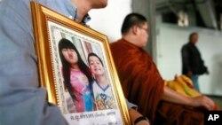 Ông Tayakorn Yos-Ubon, cha của 2 trẻ em bị thiệt mạng trong vụ nổ bom, ngồi để nhận xác con tại bệnh viện ở Bangkok, ngày 24/2/2014. Ít nhất 20 người đã thiệt mạng và hàng trăm người bị thương kể từ khi các cuộc biểu tình bùng ra hồi năm ngoái.