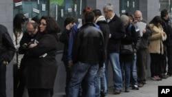 Españoles hacen fila en busca de trabajo en una oficina de empleos en Madrid.