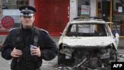 Cảnh sát canh gác phía trước một chiếc xe cảnh sát bị đốt cháy ở Tottenham, phía bắc thủ đô London, ngày 7/8/2011