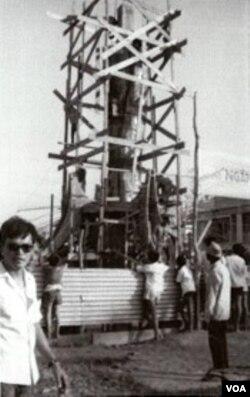 """Điêu khắc gia Mai Chửng đứng bên công trình tượng đài Bông Lúa thực hiện bằng đồng lá, cao hơn 16 m đang xây cất tại tỉnh Long Xuyên ĐBSCL; toàn cảnh pho tượng Bông Lúa tại Công viên Trưng Vương tỉnh Long Xuyên 1970; nhưng chỉ 5 năm sau, sau 30 tháng 4, 1975 tượng đài Bông Lúa ấy đã bị phá sập, quả không phải là một """"điềm lành"""". [nguồn: sưu tập Dương Văn Chung, Thatsonchaudoc.com]"""