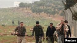 Combatientes portan sus armas mientras avanzan hacia sus posiciones cerca de la línea de frente contra las fuerzas leales al presidente sirio Bashar al-Assad en la aldea de Ratian, al norte de Alepo el 17 de febrero de 2015.