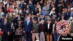 ປະທານາທິບໍດີ ຝຣັ່ງ ທ່ານເອມແມນູແອລ ມາກຣົງ ແລະປະທານາທິບໍດີ ສະຫະລັດ ທ່ານດໍໂນລ ທຣຳ ຢືນຂຶ້ນ ໃນລະຫວ່າງພິທີລຳລຶກເຖິງວັນ D-Day ຄົບຮອບ 75 ປີ ຢູ່ທີ່ສຸສານນໍມັງດີ ອາເມຣິກັນ ໃນເມືອງ ໂຄລເລີວີລ-ຊຽກ-ແມຣ ຂອງຝຣັ່ງ, ວັນທີ 6 ມິຖຸນາ 2019.