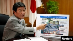 Japan's Economy, Trade and Industry Minister Toshimitsu Motegi, points to a board showing an overview of countermeasures planned for Tokyo Electric Power Co. (TEPCO)'s tsunami-crippled Fukushima Daiichi nuclear power plant, during an interview with Reuter