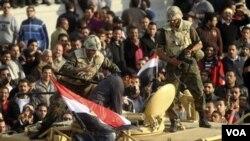 Tentara Mesir berusaha mengamankan seorang wartawan yang terluka akibat bentrokan antara penentang dan pendukung Mubarak di Kairo, (2/2).