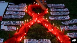 FILE - An HIV-positive Filipino lights candles around an AIDS symbol as he participates in an event in observance of World AIDS Day in Quezon city, Philippines, Dec. 1, 2016.