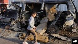 8일 이라크 바그다드 부근에서 일어난 연쇄 차량폭탄 폭발로 30여명이 사망한 가운데 사건 현장을 한 소년이 지나고 있다.