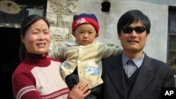 This undated photo provided by the China Aid Association shows blind Chinese legal activist Chen Guangcheng, right, with his son, Chen Kerui, with his wife Yuan Weijing, left, in Shandong province, China.